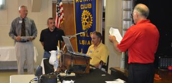 Crowley Rotarian Gene Williams and new member Tracy Young, center, look on as President Scott Shumacher, right, inducts and welcomes Young to the Rotary Club of Crowley's membership at Tuesday's meeting.
