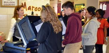 Students use real voting machines to vote.