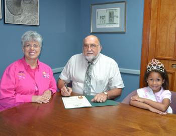 "PROJECT PINK DAY PROCLAIMED - During ceremonies at City Hall, Mayor Roland Boudreaux signed a proclamation declaring Sunday, Oct. 6, as ""Project Pink Day,"" in observance of October as Breast Cancer Awareness month and Preceptor Alpha Chi of Beta Sigma Phi lauches its ""Project Pink"" campagn. Joining Mayor Boudreaux for the proclamation were BSP Chairman Theresa Prather, left, and Zoe Traore, Tiny Project Pink Queen."